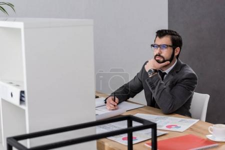 thoughtful businessman sitting at table and looking up