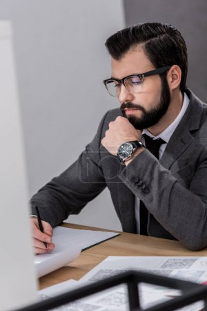 businessman sitting at table and looking at documents in office