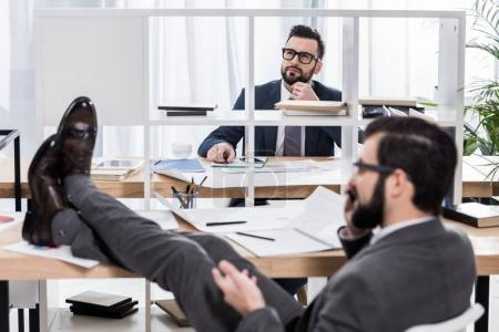thoughtful businessman trying to work when colleague talking by smartphone with legs on table