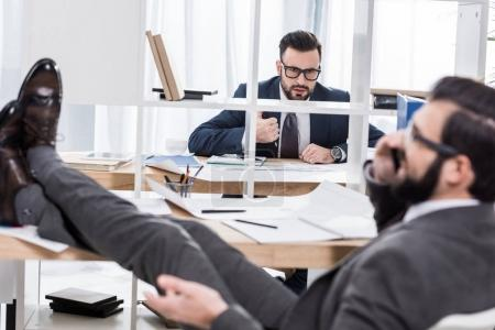 businessman trying to work when colleague talking by smartphone with legs on table