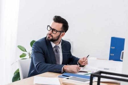 homme d'affaires pensif assis à la table de travail et de la recherche.