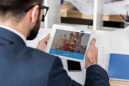 businessman holding tablet with loaded couchsurfing page
