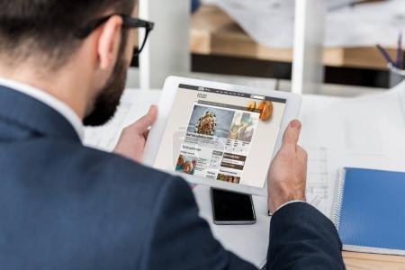 Photo pour Homme d'affaires tenant tablette avec chargé bbc food page - image libre de droit
