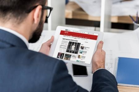 Photo for Businessman holding tablet with loaded bbc news page - Royalty Free Image