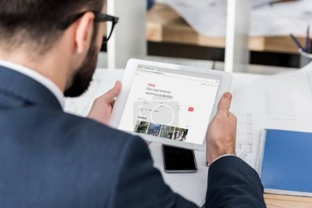 businessman holding tablet with loaded airbnb page
