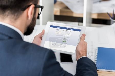 businessman holding tablet with loaded facebook page