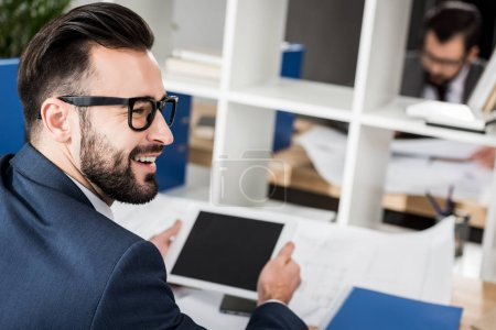 smiling businessman holding tablet at working table