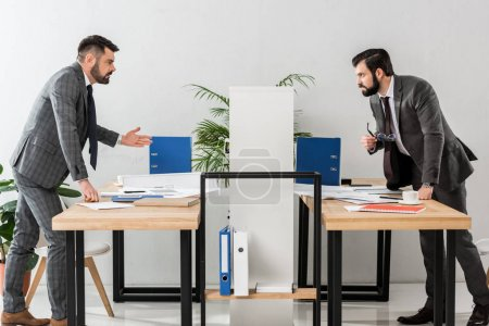 two businessmen quarreling through partition in office
