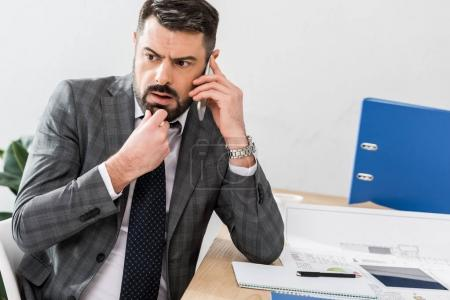thoughtful businessman talking by smartphone in office