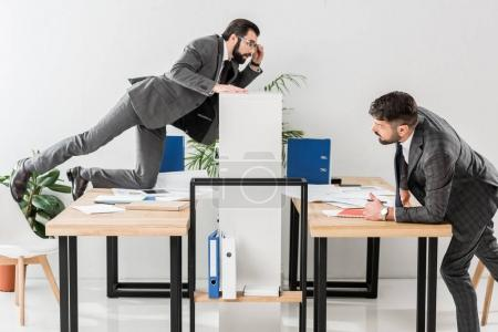 two businessmen spying on each other in office