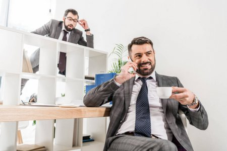 businessman spying on colleague above partition in office