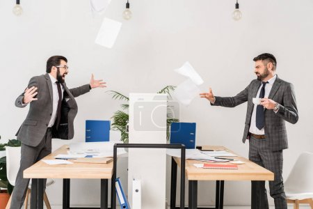 Photo for Businessmen quarreling in office and throwing documents - Royalty Free Image