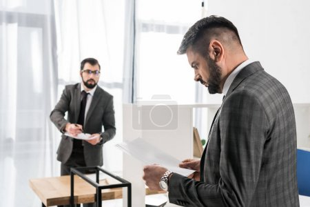 handsome businessman looking at documents in office