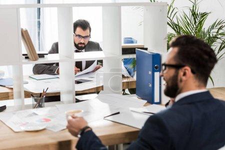 Photo pour Hommes d'affaires assis aux tables de travail avec la partition entre eux - image libre de droit