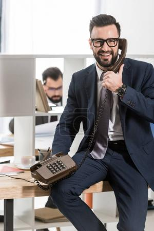 smiling businessman talking by stationary telephone in office and looking at camera