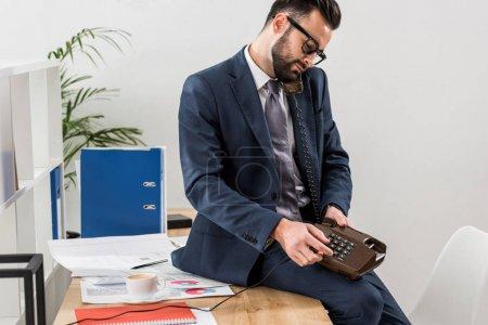 Photo pour Homme d'affaires de parler par téléphone fixe au bureau et assis sur la table - image libre de droit