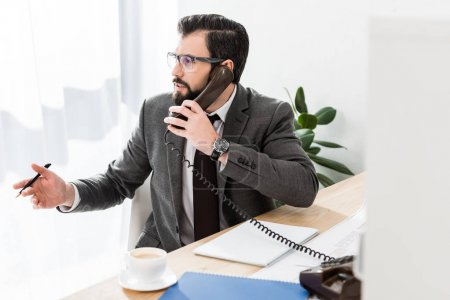 businessman talking by stationary telephone in office and looking away