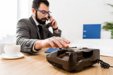 businessman dialing number with stationary telephone in office