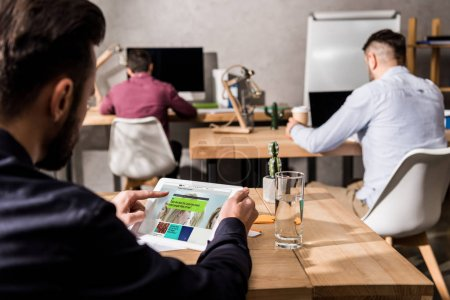 businessman holding tablet with loaded bbc science page