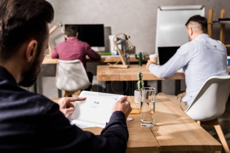 businessman holding tablet with loaded google page