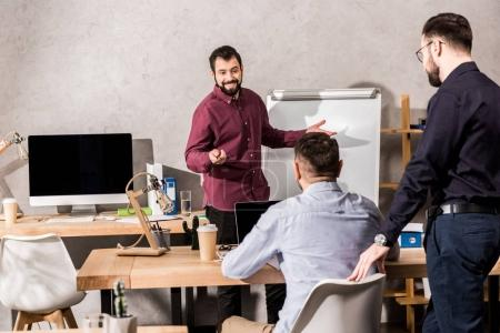 smiling businessman showing something to colleagues at flipchart in office