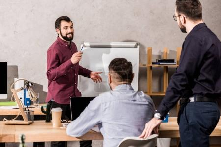 smiling businessman describing something to colleagues at meeting in office