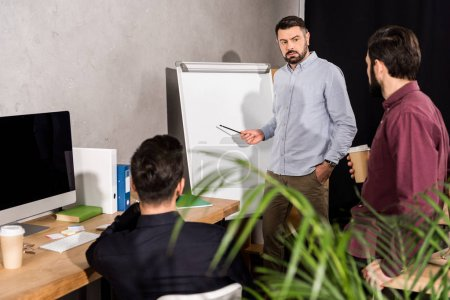 businessman describing something to colleagues at meeting in office