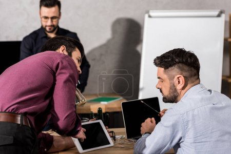 businessman showing something on tablet to colleagues