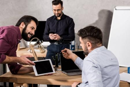 smiling businessman showing something on tablet to colleagues