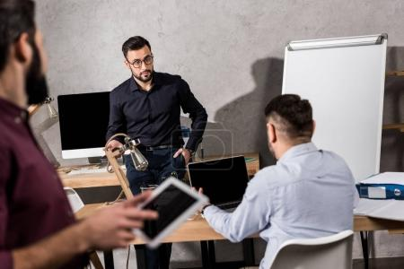 colleagues talking at office with businessman with tablet on foreground