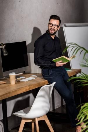 Photo pour Homme d'affaires souriant debout avec livre au bureau - image libre de droit