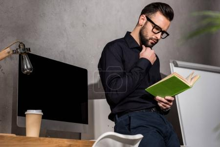 thoughtful businessman standing and reading book in office