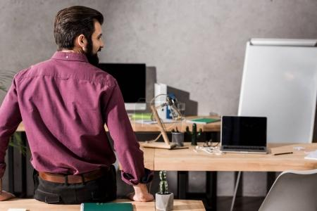 rear view of businessman leaning on table in office