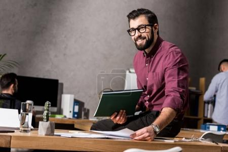 smiling businessman holding documents and sitting on table