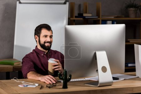 Photo for Smiling businessman working at computer in office - Royalty Free Image