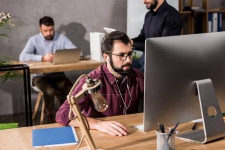 Photo pour Homme d'affaires travaillant à l'ordinateur de bureau et d'écoute de musique avec des écouteurs - image libre de droit