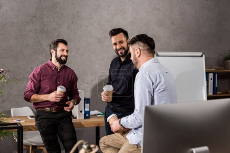smiling businessmen talking during coffee break at office