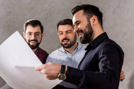 smiling architects looking at blueprints at working space