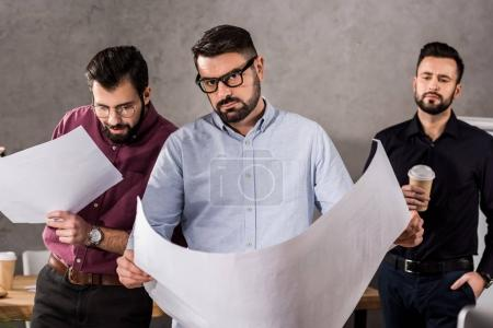 handsome caucasian architects with blueprints in office