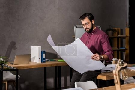 thoughtful handsome architect looking at blueprint in office
