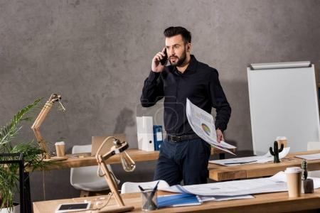 architect holding blueprints and talking by smartphone in office