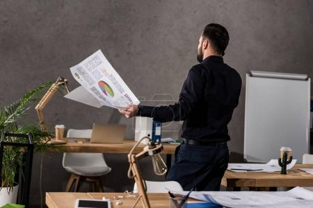 rear view of architect holding blueprints and talking by smartphone
