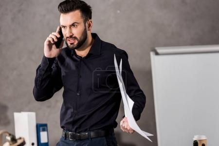 irritated architect holding blueprints and talking by smartphone