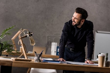 smiling architect leaning on working table and looking away