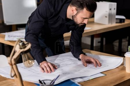 handsome architect looking at blueprints on table