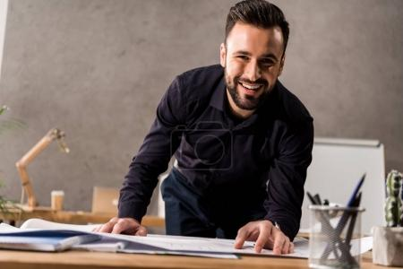 smiling architect touching blueprints and looking at camera