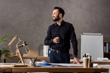 smiling architect standing near working table and looking away