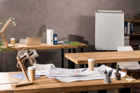 Photo for Working tables with blueprints, coffee and supplies - Royalty Free Image
