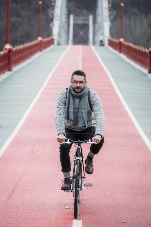 handsome adult man in sweater riding bicycle on pedestrian bridge