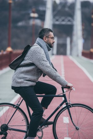 side view of handsome adult man riding bicycle on pedestrian bridge